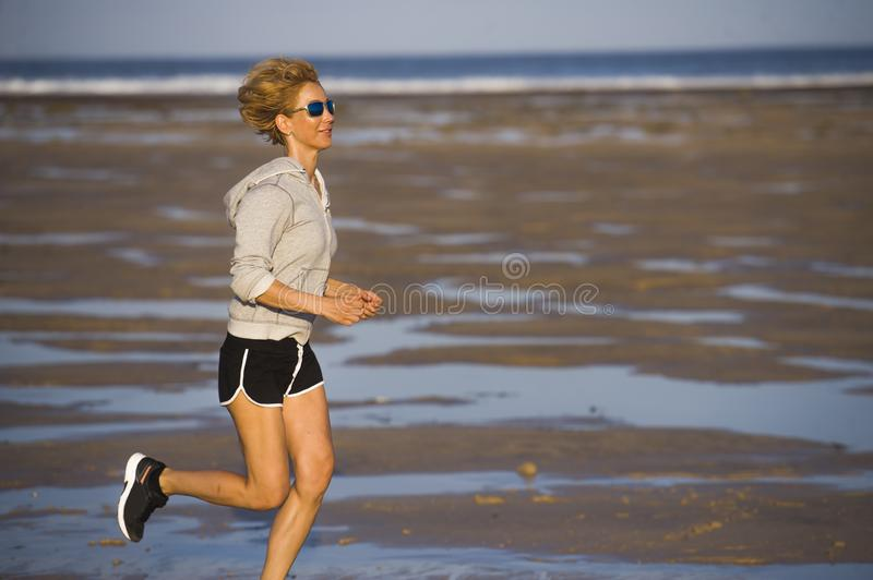 Isolated background portrait of young happy and attractive fit woman running on the beach in outdoors jogging workout in fitness t. Raining and healthy sporty stock image