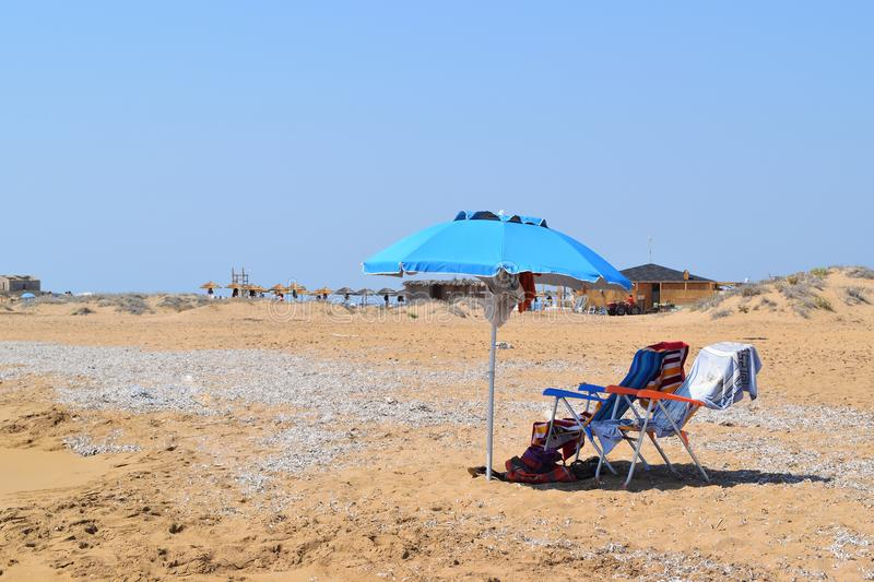Isolated beach umbrella and deck chairs royalty free stock photos