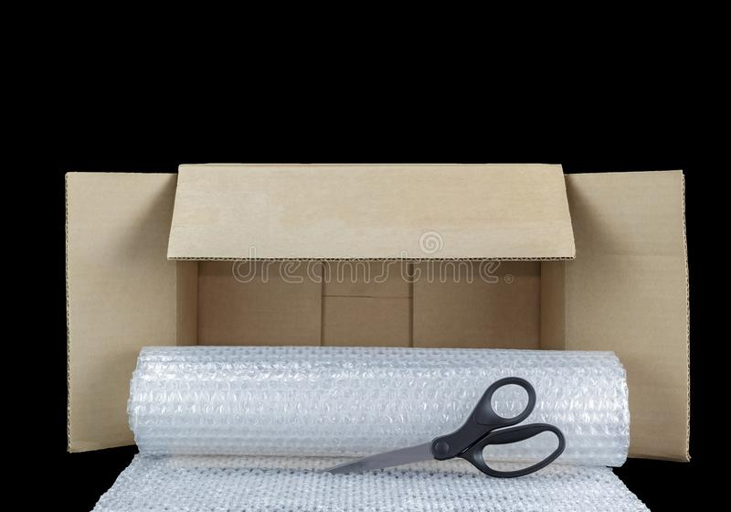 Scissors, roll of bubble wrap, and open brown cardboard box. stock image