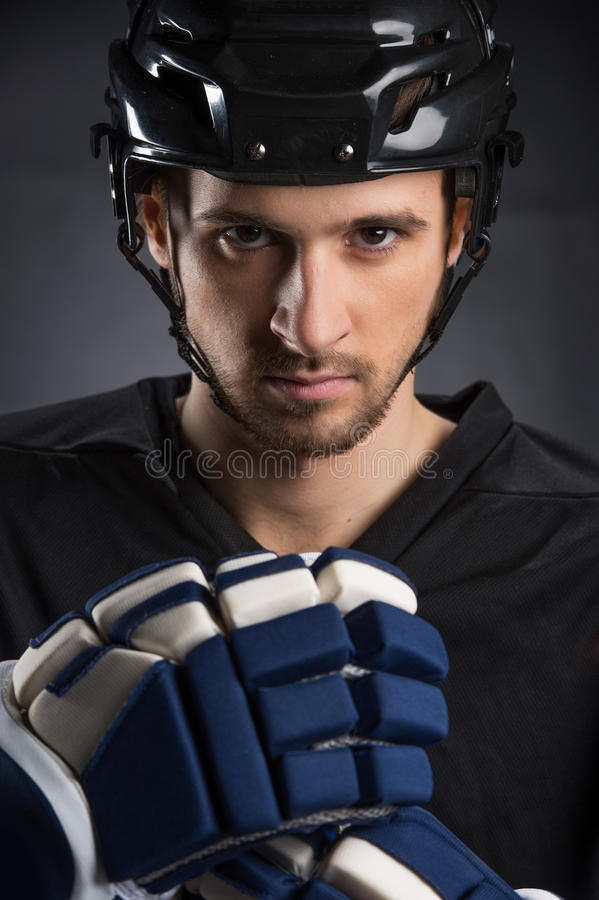 Isolated on black. Portrait of handsome hockey player in black helmet royalty free stock photo