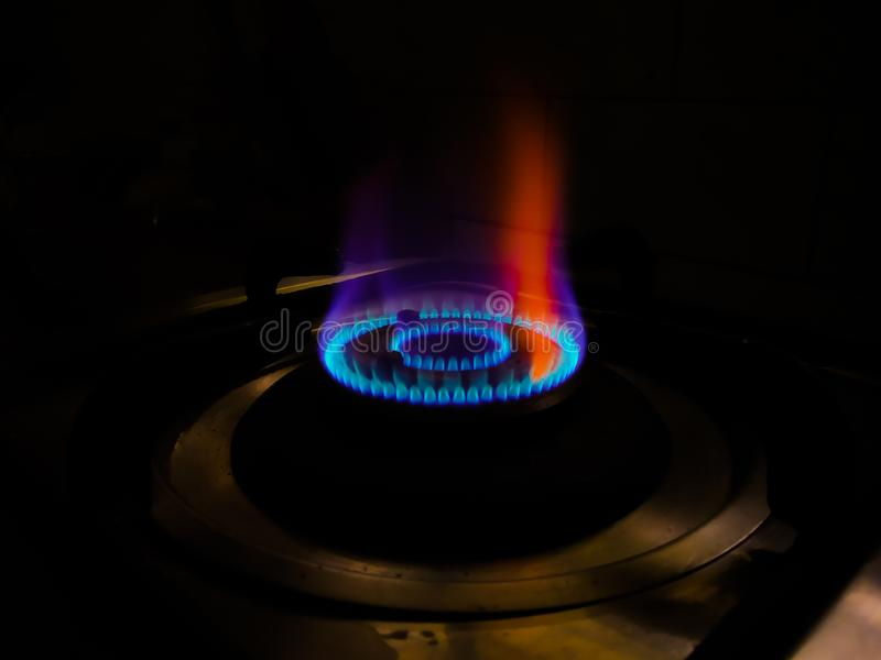 Isolated blue flame with orange shade of gas burner at black background royalty free stock image