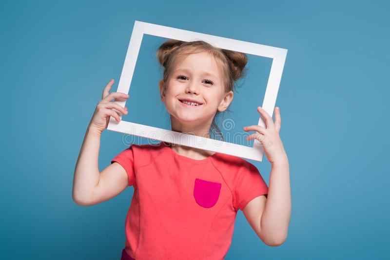 Beautiful cute little girl in pink dress holds picture frame stock image