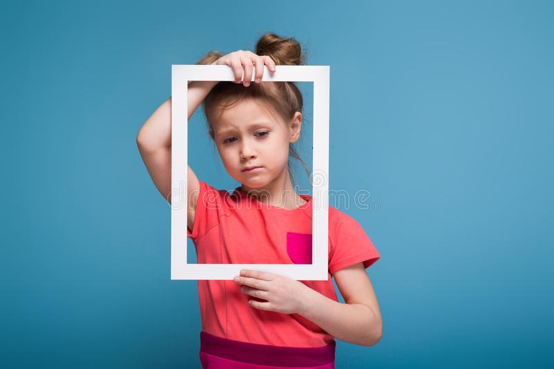 Beautiful cute little girl in pink dress holds picture frame royalty free stock image