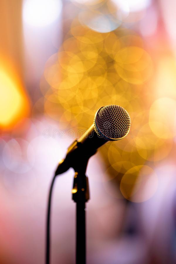 Isolated bokeh microphone on a concert stage with artists redy to perform in the backstage royalty free stock photos