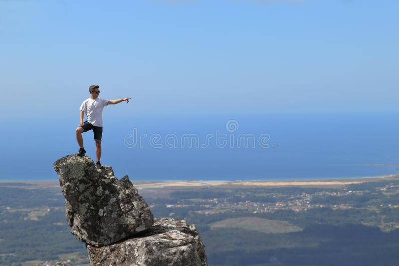 ISOLATED BOY POINTING FROM THE TOP OF A ROCK NEAR THE OCEAN ON SUMMER HOLIDAY stock photos