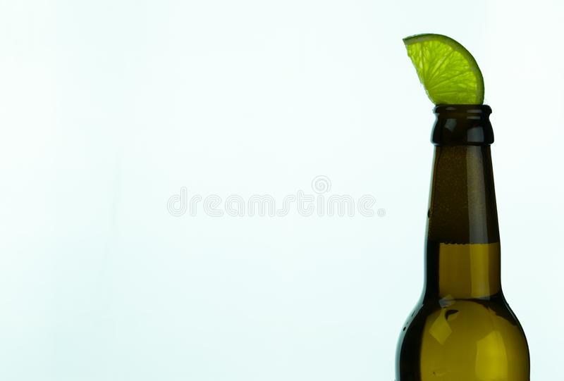 Isolated brown beer bottle with a slice of green lime on a white background. And copy space stock photos