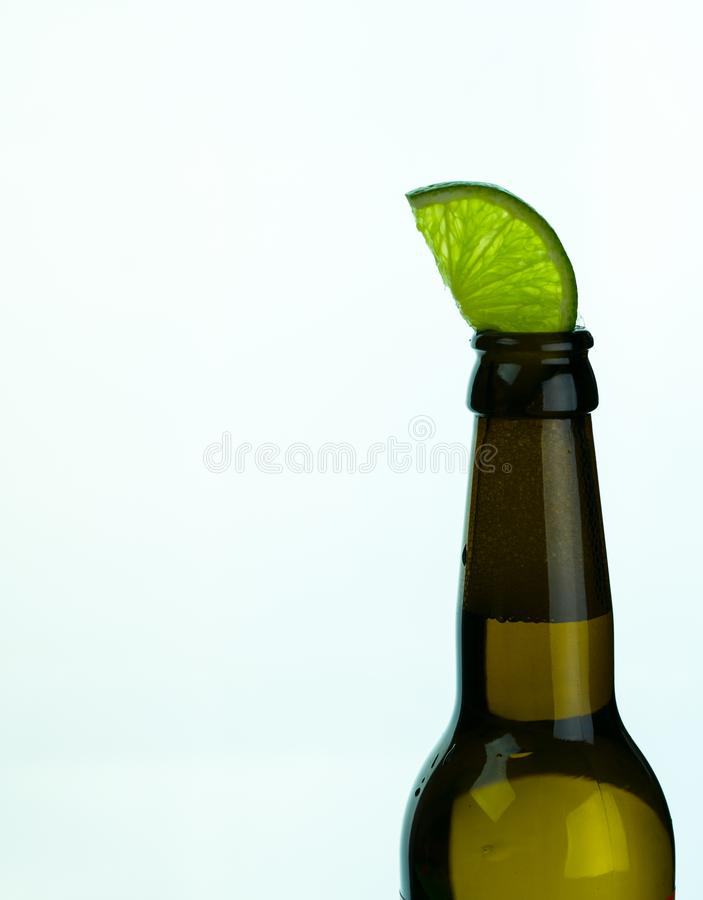 Isolated brown beer bottle with a slice of green lime on a white background. And copy space royalty free stock image