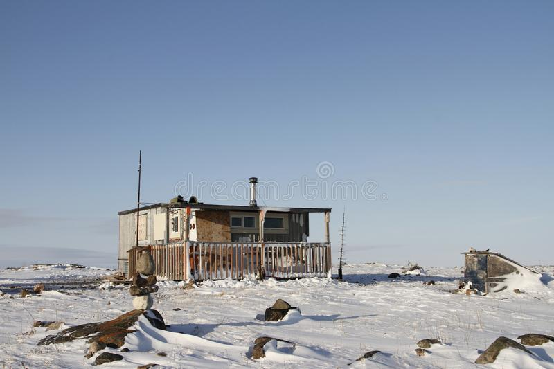 Isolated cabin on snowy ground with a small Inukshuk in front stock photography