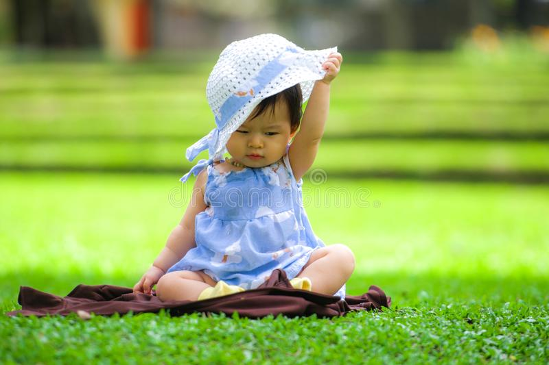 Isolated candid portrait of sweet and adorable Asian Chinese baby girl 3 or 4 months old playing with hat alone at city park royalty free stock image