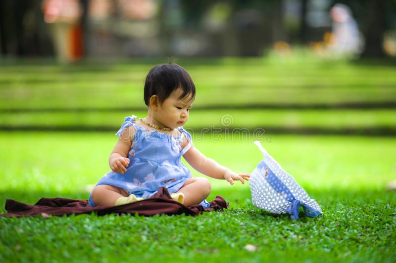 Isolated candid portrait of sweet and adorable Asian Chinese baby girl 3 or 4 months old playing with hat alone at city park royalty free stock photos
