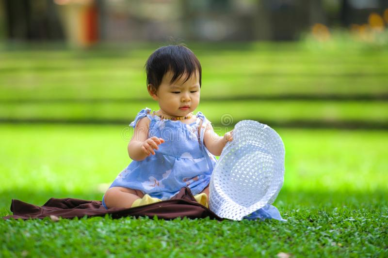Isolated candid portrait of sweet and adorable Asian Japanese baby girl 3 or 4 months old playing with hat alone at city park stock photos