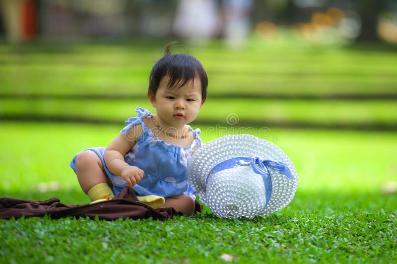 Isolated candid portrait of sweet and adorable Asian Korean baby girl 3 or 4 months old playing with hat alone at city park royalty free stock image