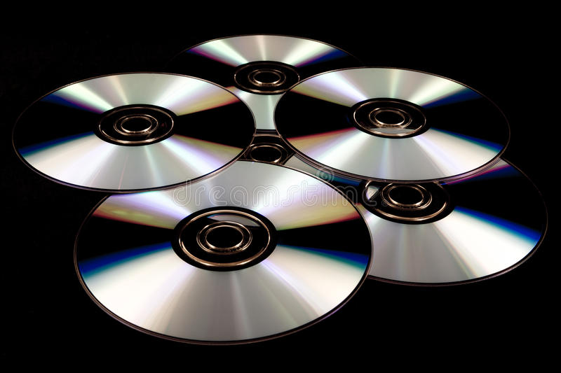 Isolated CD and DVD. Isolated blank music and data CD and DVD on a black backdrop royalty free stock photos