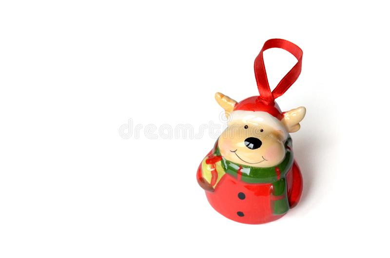 Isolated ceramic figure with pendant. Christmas deer in a red suit and hat in a green scarf with a gift on white background. royalty free stock photos