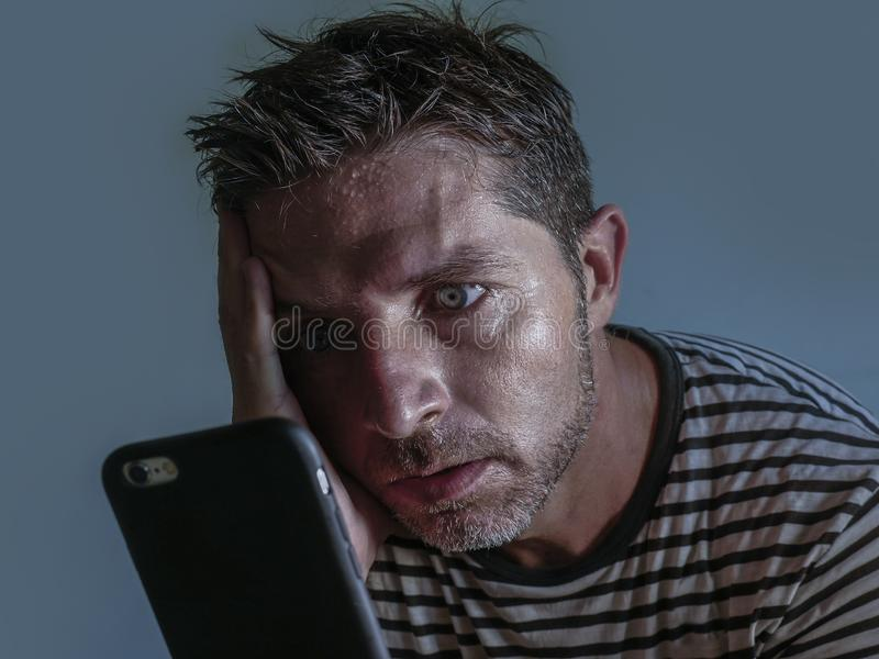 Isolated close up face portrait of young attractive and stressed man using mobile phone feeling worried and frustrated looking stock images