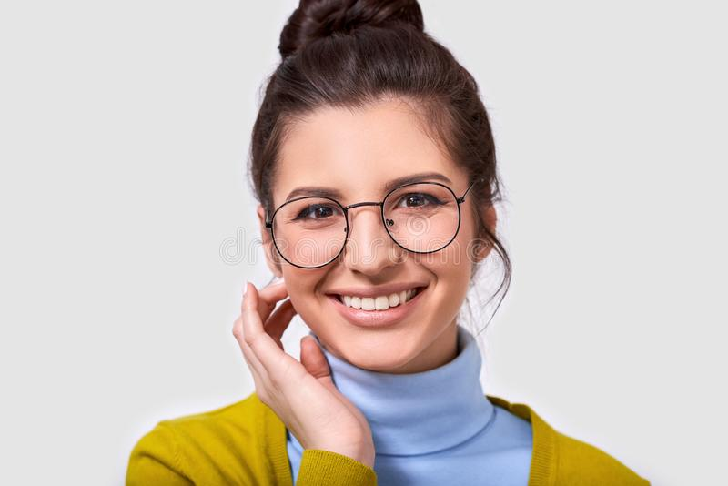 Isolated closeup image of pretty young woman, smiling and wearing casual outfit and eyeglasses. Caucasian brunette female in blue stock photo