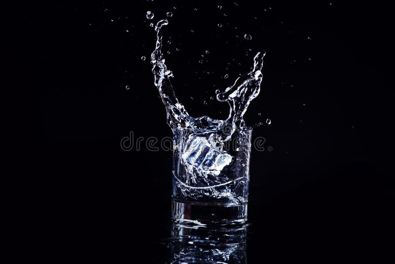 Isolated cold water in a glass with splash and cubes of ice on black background, brandy in a glass royalty free stock photo