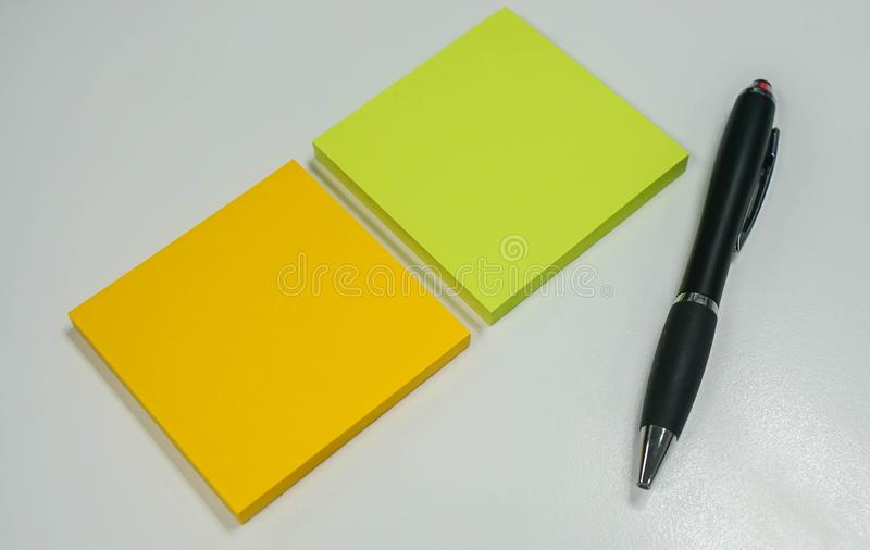 Isolated sticky note with pen for business message in office. Isolated colorful sticky note with pen for business message in office royalty free stock images
