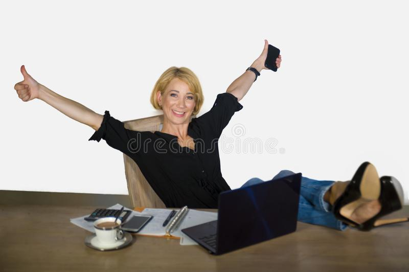 Isolated corporate business portrait of young beautiful and happy woman with blonde hair working relaxed at office laptop computer. With feet on desk royalty free stock photos