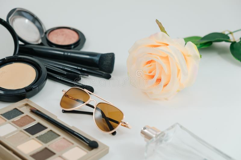isolated cosmetic object, powder, glasses, perfume bottle and rose on white background with copy space. image for stock photography