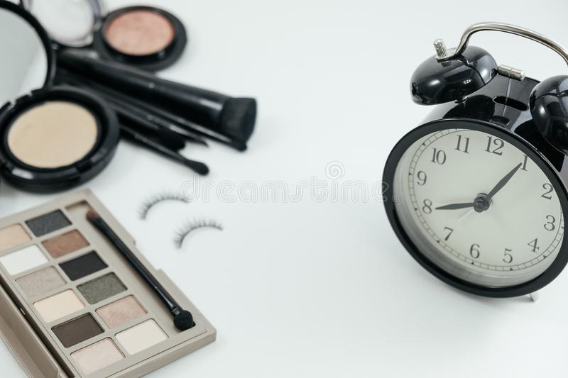 isolated cosmetic product, powder, eyelash and alarm clock on white background with copy space. image for royalty free stock photo