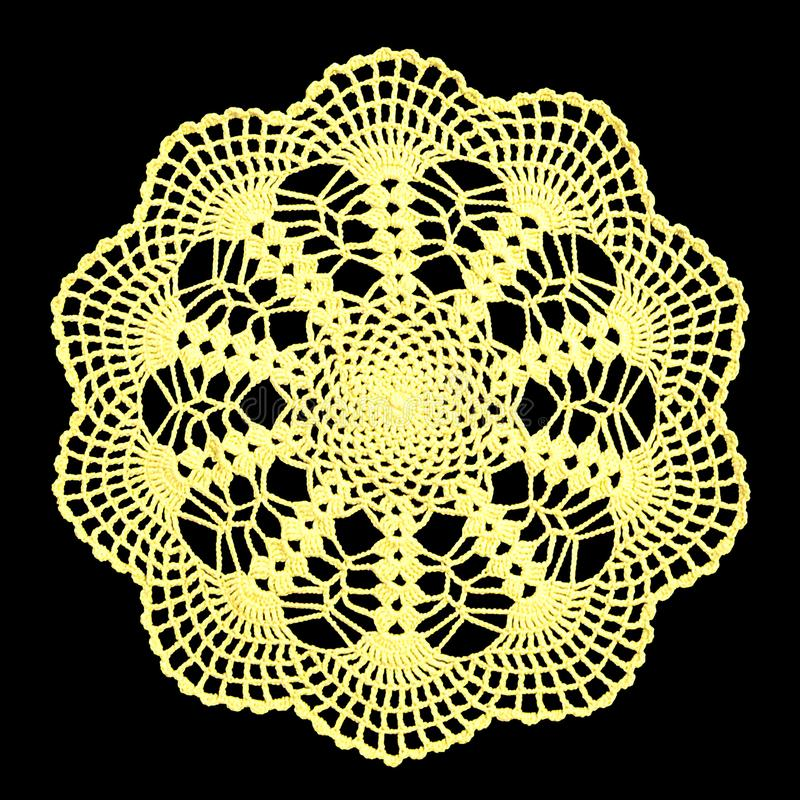 Isolated crocheted bright lime color doily with a pattern of arches on a black background. Round decorative cotton doily. Top view stock photography