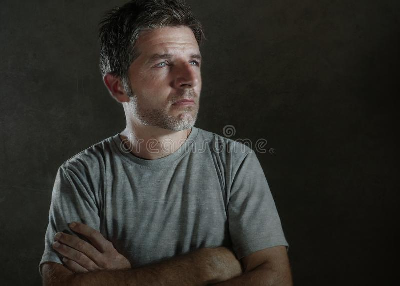Isolated dark background portrait of 30s to 40s sad and depressed man looking thoughtful and worried suffering depression problem royalty free stock photography