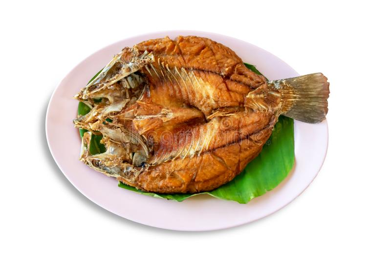 Isolated fried snapper fish on Banana leaves in dish on a white background with clipping path royalty free stock photo