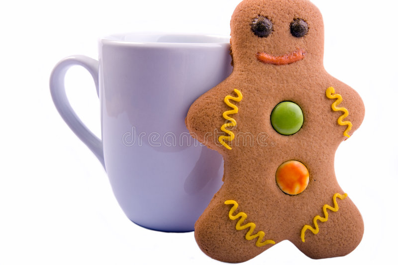 Isolated Gingerbread Man and M. A gingerbread man leaning against a cup against a white background stock photos