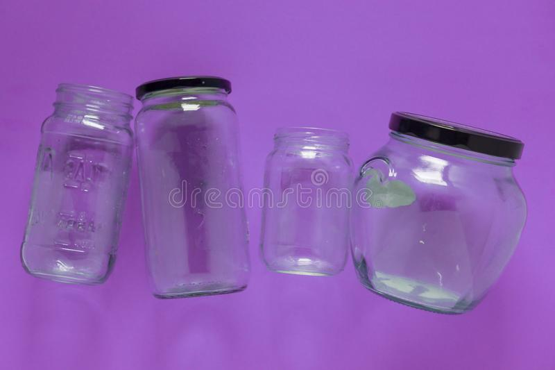 Isolated glass jars, flat and center on violet purple background - recycling royalty free stock photography