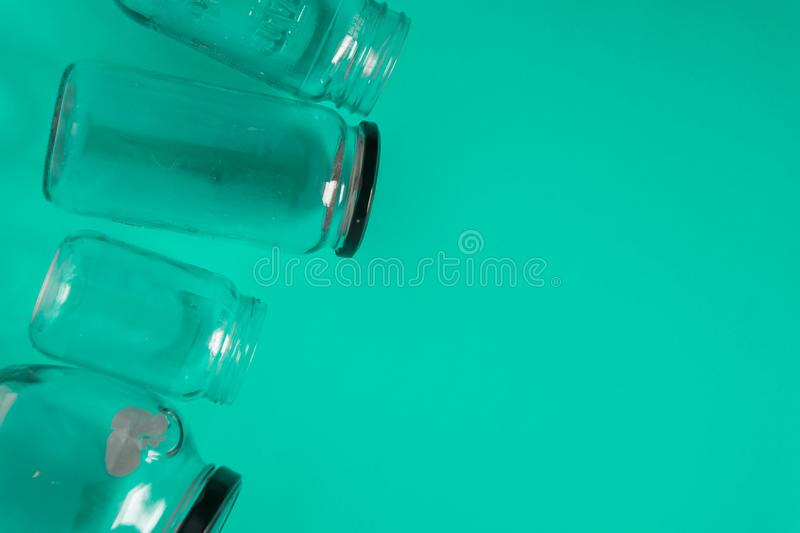 Isolated glass jars, flat on teal mint green background, room copy space right. Isolated glass jars, flat on teal mint green background, blank empty room space stock image