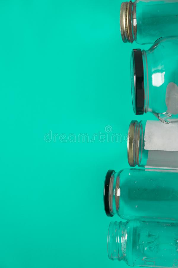 Isolated glass jars, flat on teal mint green background room, copy space on left. Isolated glass jars laid flat on teal mint green background, blank empty room royalty free stock images