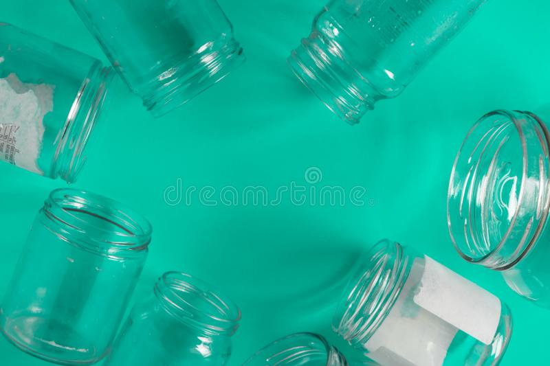 Isolated glass jars, no lids flat, teal mint green background, copy space room. Isolated open glass jars, flat on teal mint green background, blank empty room stock photography