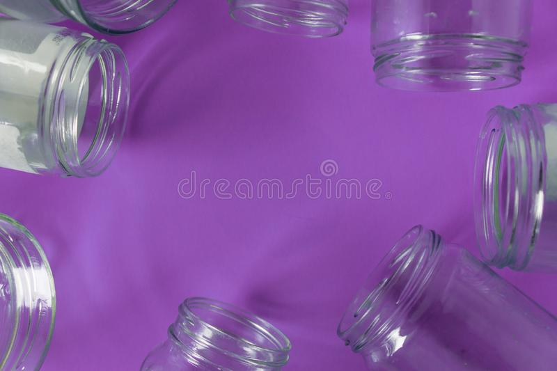 Isolated glass jars, no lids flat, violet purple background, copy space room stock photography