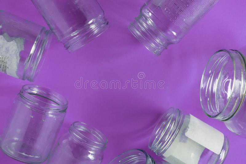 Isolated glass jars, no lids flat, violet purple background, copy space room royalty free stock photography