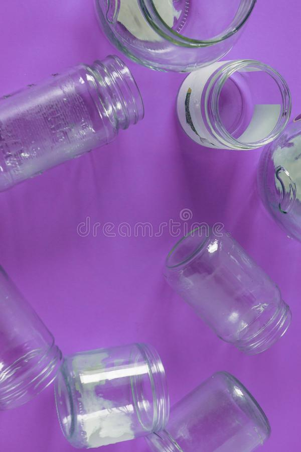 Isolated glass jars, no lids flat, violet purple background, copy space room royalty free stock photos