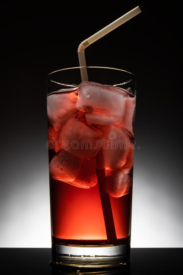 Isolated glass with a red cocktail and ice-cubes royalty free stock image