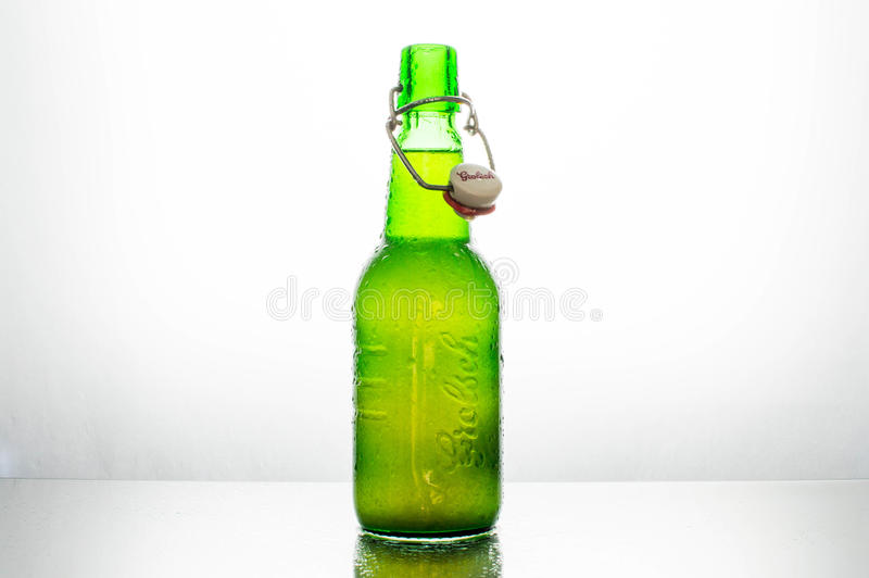 Isolated green bottle of Grolsch beer on a white background lighted from behind stock photos