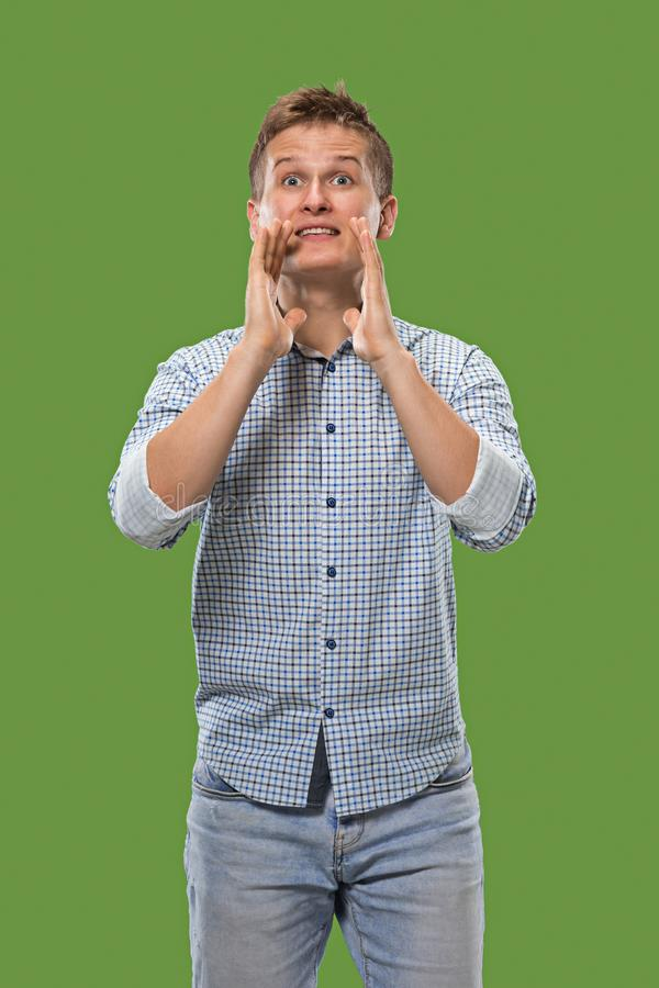 Isolated on green young casual man shouting at studio stock photography