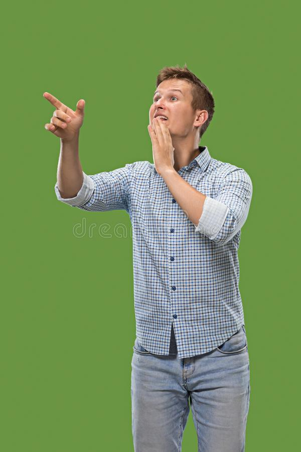 Isolated on green young casual man shouting at studio stock image