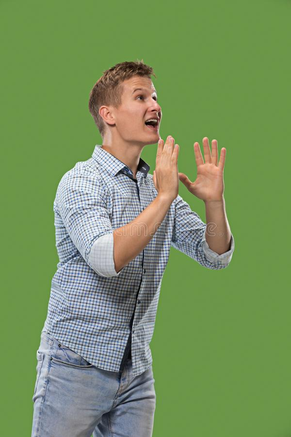 Isolated on green young casual man shouting at studio royalty free stock photography