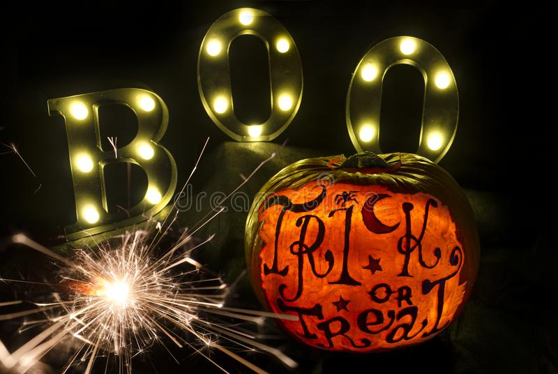Halloween Pumpkin Display with Scary Face and Sparklers. Isolated Halloween Pumpkins with scary face and writing and a trail of Sparklers royalty free stock photo