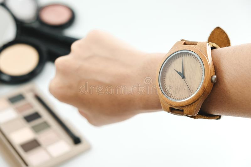 isolated hand of woman wearing wooden watch with cosmetic product, powder, brush on white background. image for copy royalty free stock image