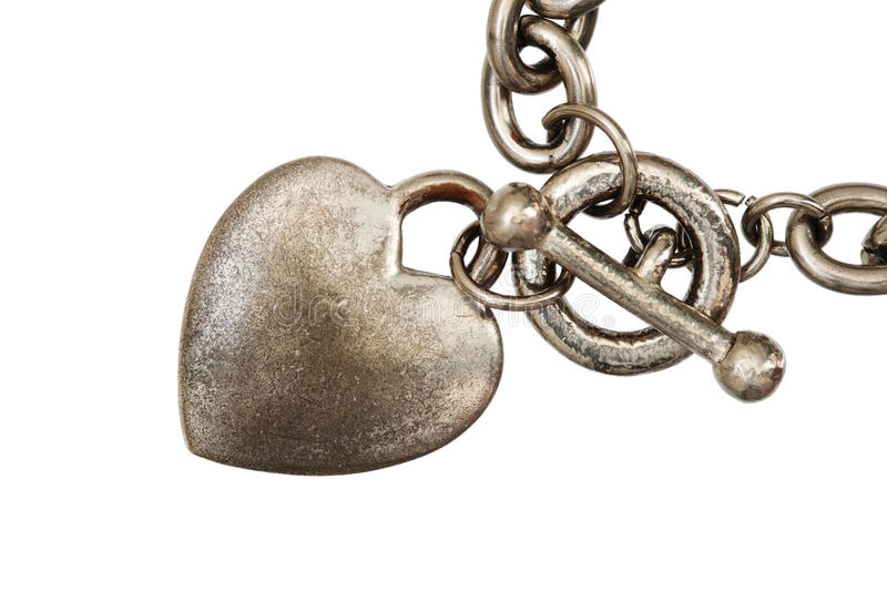 Isolated heart charm macro. Old silver heart charm on a chain isolated on white background royalty free stock image