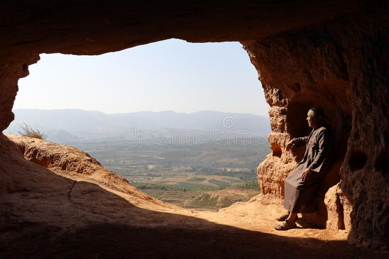ISOLATED HERMIT MAN WITH DJELLABA AND PALESTINIAN SCARF SITTING AT THE ENTRANCE OF A CAVE ON THE HIGH OF A MOUNTAIN stock photos