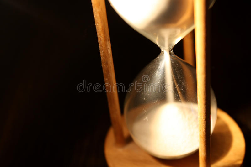 Isolated hourglass. Time is running out too quickly to perceive it -- An hourglass isolated on a black background