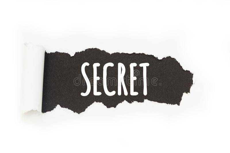 Isolated inscription `secret` on a black background, paper rupture. royalty free illustration