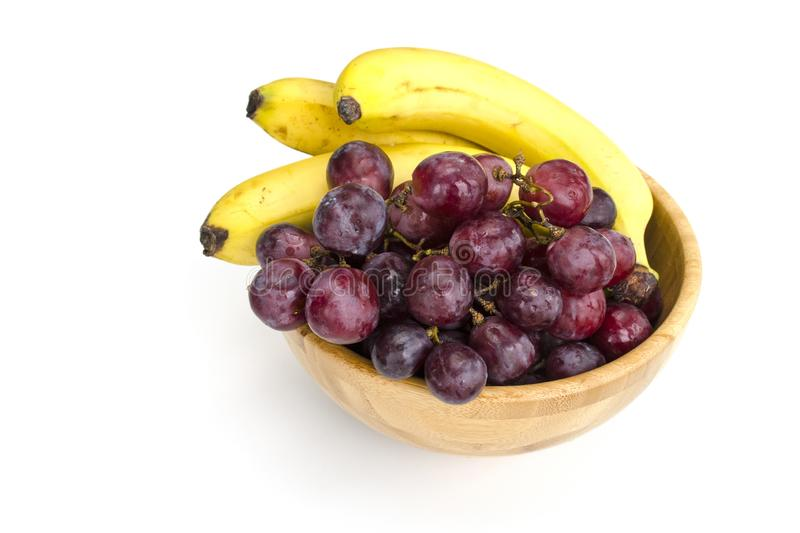 Isolated juicy clusters of large red grapes and ripe bananas in a wooden bowl stock images