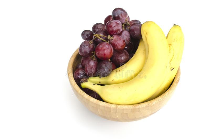 Isolated juicy clusters of large red grapes and ripe bananas in a wooden bowl royalty free stock image