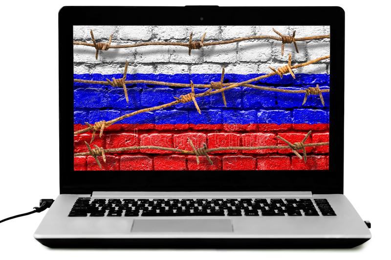 Isolated laptop with rusty barbed wire and Russian flag painted on a brick wall on the screen stock photography